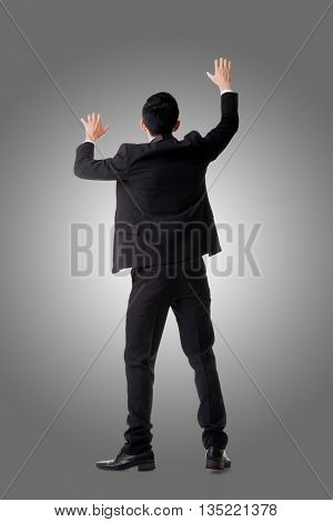 Asian businessman climbing, full length portrait isolated