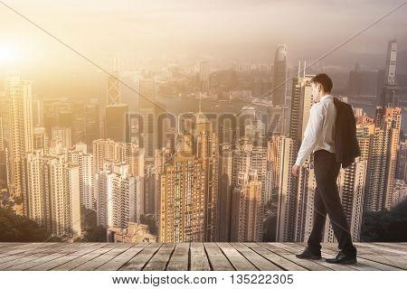 Businessman walking with copyspace on sky.