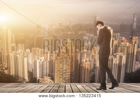 Businessman walking and thinking with copyspace on sky.