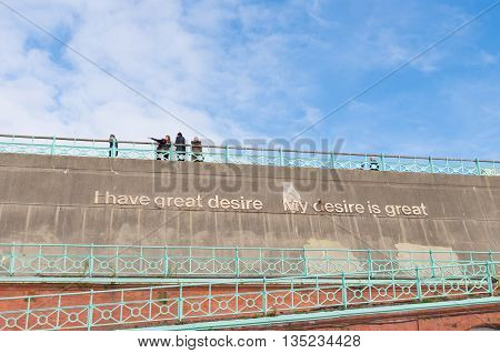 BRIGHTON UK - OCTOBER 20 2015: Concrete sea wall with saying: I have great desire - My desire is great