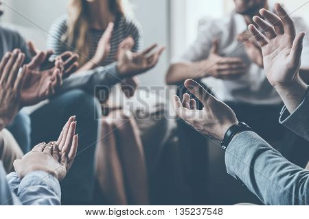 Applauding their success. Close-up of people applauding while sitting in circle together