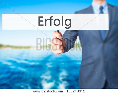 Erfolg (success) - Businessman Hand Holding Sign