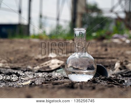 Chemical glassware retort with water standing on the ground among the debris. The concept of ecology environment water pollution