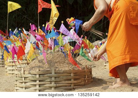 Songkran festival, Buddhist monk make sand chedi and pin traditional flags, Chiangmai, Thailand.