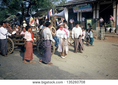 PAGAN / MYANMAR - CIRCA 1987: Men dance to music from a loudspeaker carried by a cart in a Buddhist parade in Pagan during a holiday.