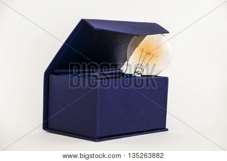 Bulb in blue box against white background with copy space signifying thinking outside the box concept