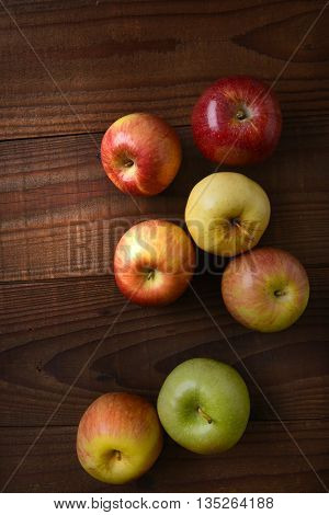 Different varieties of fresh picked apples on a rustic wood table. Fuji, Gala, Granny Smith, Braeburn, Golden Delicious Shot from a high angle.