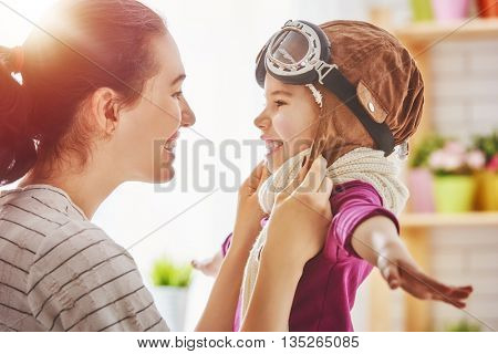 Happy family is preparing for a costume party. Mother and her child girl playing together. Girl in pilot's costume.
