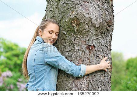 Young beautiful woman hugging tree trunk
