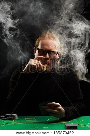 Young red-haired bearded man in glasses and black pullover with a cigar and cards sitting at poker table covered with green cloth in a puff of smoke.
