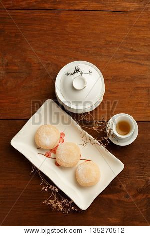 Beautiful delicious mochi rice cakes on white ceramic square plate with porcelain asian tea-set green tea and dried flowers standing on brown wooden table.