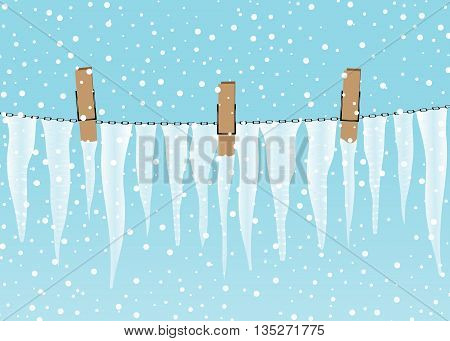 winter. A rope with clothespegs, icicles and snowfall against the blue sky