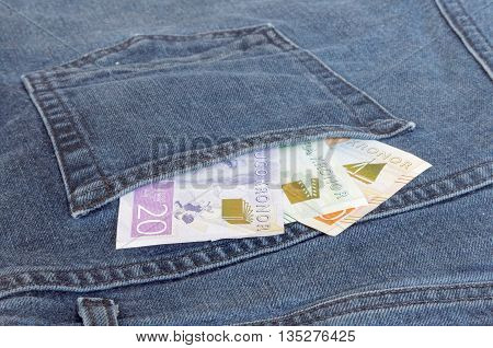 Swedish bank notes sticking up from a jeans pocket