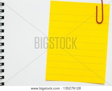 Yellow line memo paper clipped on white spiral notebook - line paper clipped on white binder notepad