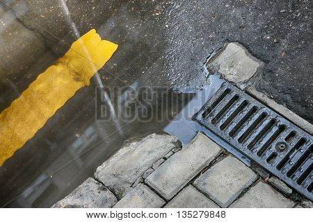 puddle on road at drainage metal grill of drainage tray on sidewalk