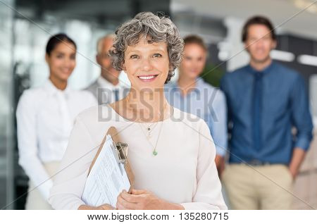 Happy senior business woman standing with team. Human resource manager looking at camera and holding progress report of employee. Happy senior businesswoman standing with business team in background.