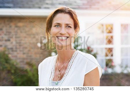 Portrait of a woman standing outside house and thinking. Cheerful mature woman smiling and looking up. Young happy woman daydreaming outdoor.