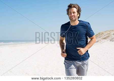 Mature man listening to music while jogging on the beach. Runner working out wearing earphones listening to music playlist. Man listening to music with mp3 player in armband and jogging at beach.