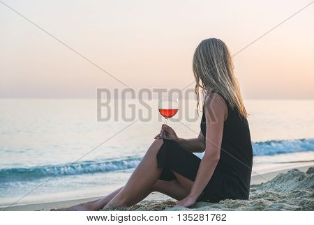 Young blond woman enjoying glass of rose wine on beach by the sea at sunset. Kleopatra beach, Alanya, Mediterranean region, Turkey.