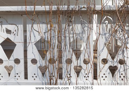 Thread on white wooden veranda with vine brunches