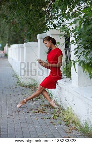 Beautiful girl in red dress and in pointe shoes reading a book outdoors