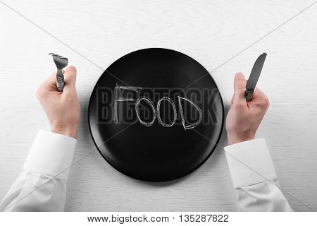 Man holding fork and knife with empty plate. Hunger concept