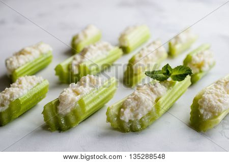 Celery with cream cheese selective focus on a white background