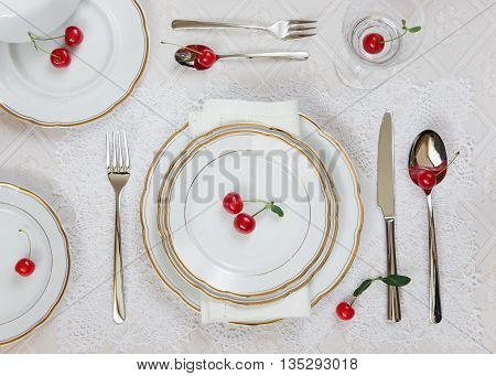 Beautifully decorated table with white plates crystal glasses linen napkin cutlery and red cherries on luxurious tablecloths; top view