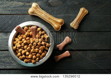 Dog food in metallic bowl on black wooden background