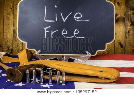 357 magnum revolver in leather holster on American flag with six bullets in front of chalkboard reading live free