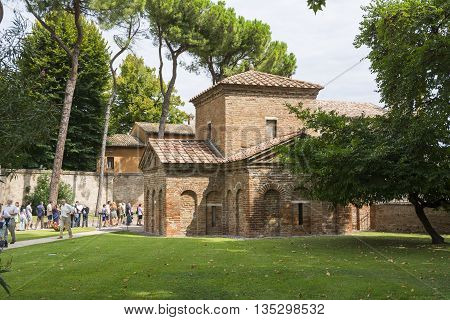 RAVENNA,ITALY-AUGUST 21,2015:couple stroll near the Galla Placidia mausoleum from the San Vitale garden's during a cloudy day.
