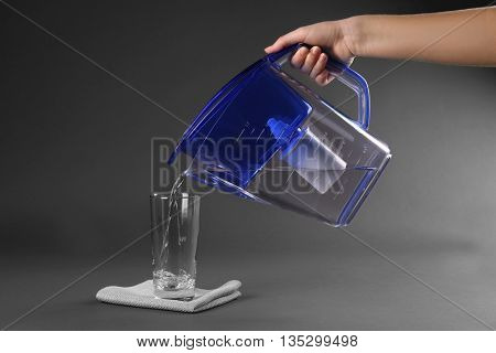 Purified water pouring into glass on grey background