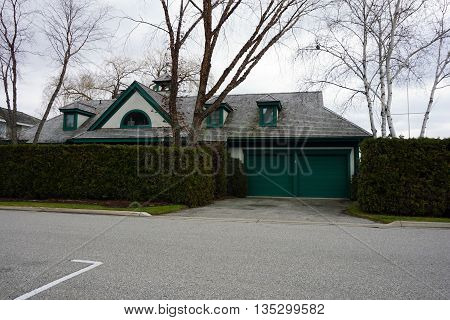 HARBOR SPRINGS, MICHIGAN / UNITED STATES - DECEMBER 24, 2015: A lakefront home, behind an arbiorvitae (Thuja occidentalis) hedge, near the Zorn Park Beach in Harbor Springs.