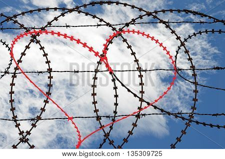 Barbwire fence with natural heart shape (digitall coloured red) on sky background. Love, freedom, peace and compassion concepts