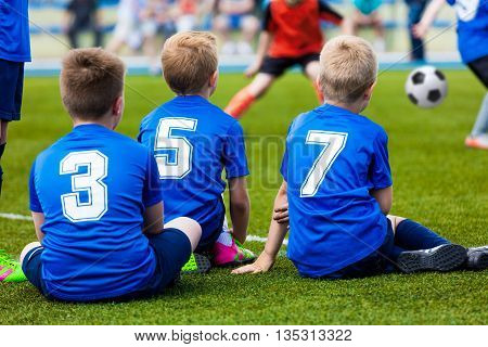 Young soccer team. Reserve players sitting together and watching football soccer tournament match for youth teams.