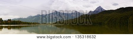 Lake in the German Alps with a chain of mountain peaks on the horizon. Reflection of the sky in water, toned photo