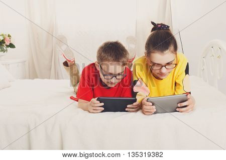 Two children, siblings on parents' bed at morning with tablets. Brother and sister play computer games. Siblings and gadgets. Children in glasses. Girl and boy play at device
