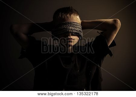 Boy Blindfolded With Hands Behind Head
