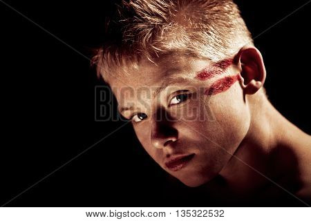 Serious Boy With Red Painted Lines On Head