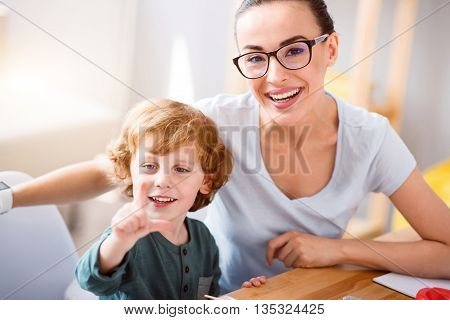So happy. Amazing contended young woman smiling and looking at the camera while sitting with her charming little boy at the table poster