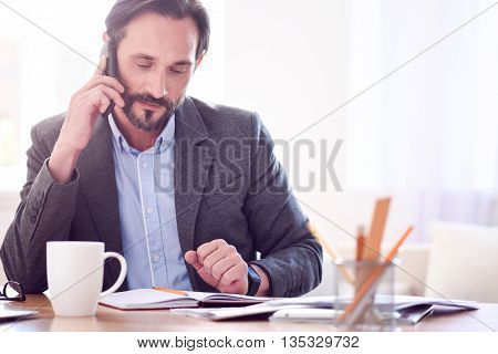 Responsible for negotiation. Calm serious businessman speaking on the phone while sitting at the table and looking at his notes