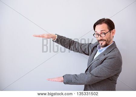 It is good. Delighted middle aged man keeping hands in gesture of holding a product while standing isolated on the grey background