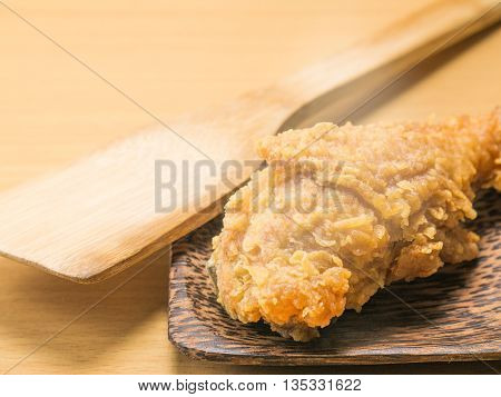 fried chicken on a plate set on a wood table background