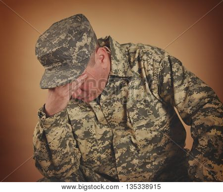 An army soilder man is wearing a uniform and is sad and upset covering his eyes. Use it for a PTSD or military loss concept.