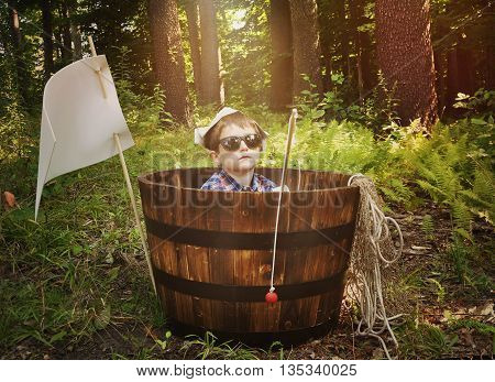 A young boy is relaxing in a wooden boat barrel with a fishing pole toy in the woods for a imagination activity or recreation concept.