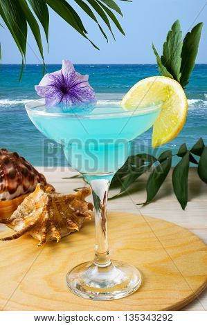 Blue Hawaiian cocktail on the tropical beach. Iced blue cosmopolitan cocktail. Blue Lagoon margarita martini cocktail. Summer beach alcohol drink