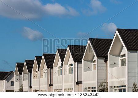 row of white houses against blue sky