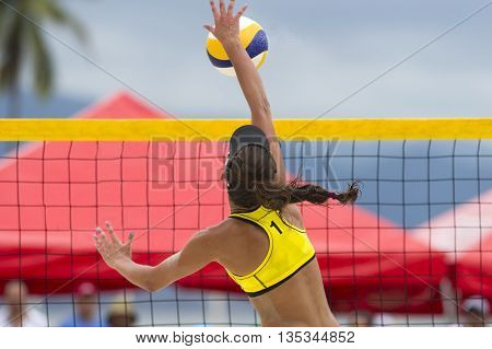 Volleyball player is a female athlete volley ball player rising up to the net to hammer the ball down.