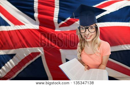 people, national education, knowledge and graduation concept - smiling young student woman in mortarboard and eyeglasses with encyclopedia book over english flag