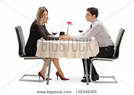 Young man apologizing to his girlfriend seated on a date isolated on white background